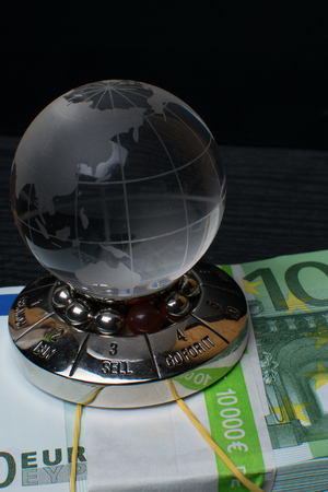 glass earth with choice and big amount euro cash 500, 100 on the black wooden background Stock Photo