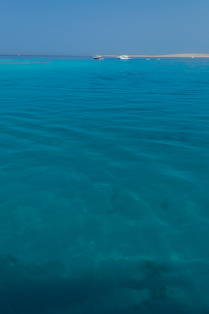 yacht in the distance sailing across the horizon in red sea with coast in the background