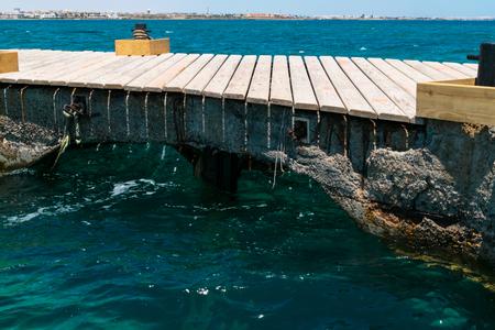 Beautiful view of concrete, wooden bridge in sea