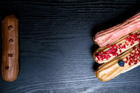 French traditional eclair, decorated with raspberry, blueberry,cream and coffee beans on black background