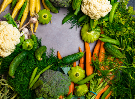Fresh vegetables. Carrot, green pea, cauliflower, cucumber, broccoli, garlic, dill, parsley, patissons on a grey background. Harvest gardening concept. Healthy food. Vegetarianism Clean eating Space for text Making salad ingredients