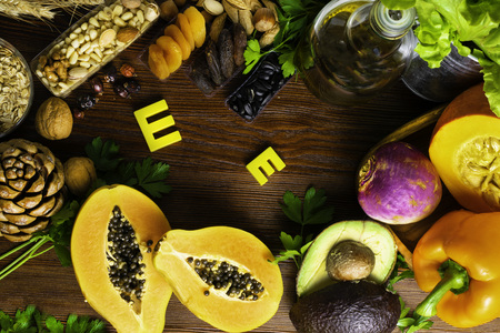 Foods containing and rich in vitamin E on a wooden board. Health food concept. Stock Photo