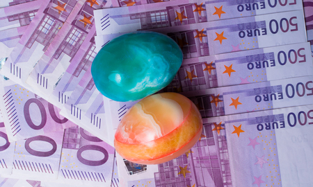 Money background - Five hundred 500 euro bills banknotes with color eggs, pile, top view Stock Photo