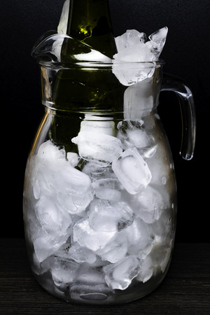 Champagne or White wine bottle in cold ice decanter isolated on black background