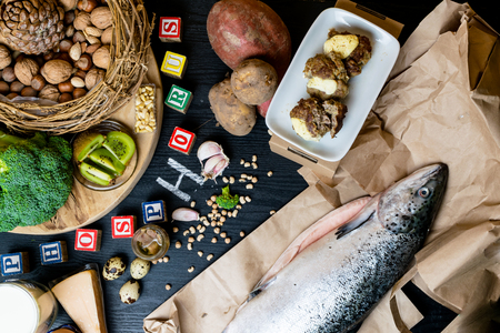 Products containing phosphorus salmon fish, pine nuts, peanuts, anchovy, cheese, milk, eggs, broccoli, kiwi, potatoes, meat, beans garlic on a round cutting board and black wooden background Stock Photo