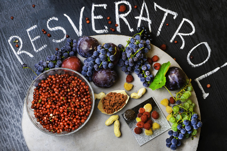 food rich with resveratrol, grapes, plums, goji, peanuts, cranberry,raspberrys dark chocolate on black wooden background