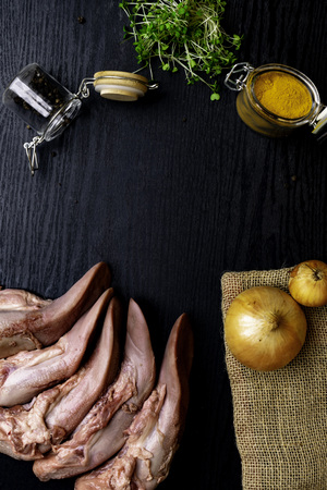 raw pork or beef tongues with black pepper and yellow spices turmeric,, in glass jar, onion on sackcloth, cress salad on black wooden table, gourment food conception Stock Photo