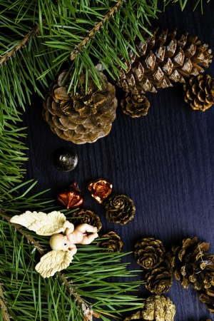 on a dark wooden background pine branches and decor, angel, cones, small teapot, red Christmas toy, free space for text Banco de Imagens