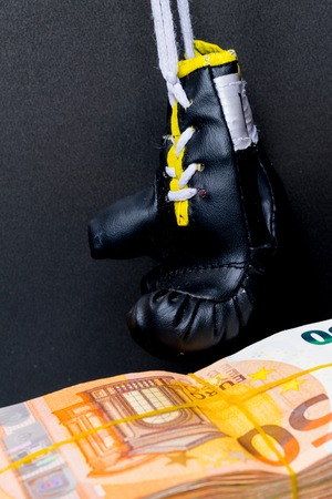 Black boxing gloves and money. Concept of bribery, dishonesty in sport, greed. Isolated on black