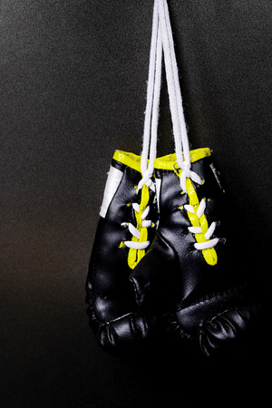 professional black boxing gloves hanging on black background with copy space. Foto de archivo