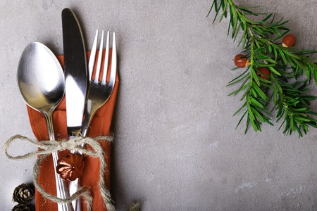Christmas and New Year table setting. Holiday decoration, spoon, fork, knife on napkin, with rope, cones, Christmas tree branch on grey stone table, copy space