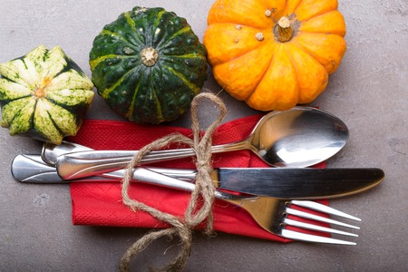 Autumn background from fallen red leave and pumpkin with silver place setting on stone table in red napkin. Thanksgiving day concept