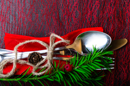 Christmas and New Year holiday table setting, fork, spoon, knife with thread , Christmas tree branch and berry, spruce cones. Celebration place setting for dinner decorations. Copy space. Top view. Stock Photo