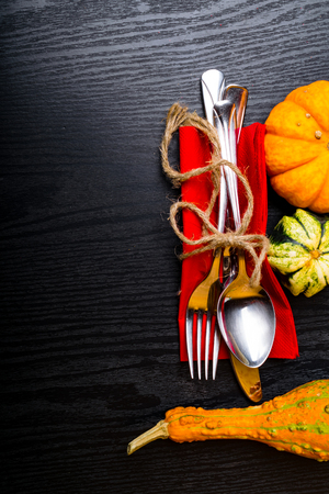 Autumn background from pumpkins, spoon, fork, knife set with thread bow, vintage place setting on black wooden table. Thanksgiving day concept