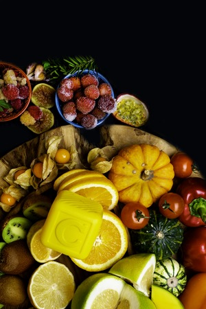 Vitamin C in fruits and vegetables. Natural products rich in vitamin C as oranges, lemons, pepper, kiwi, parsley leaves, garlic, bananas, mango, cabbage, melon, berry, pumpkin, tomatoes, mango, persimmon, passion fruit physalis kiwi fig raspberry strawberry pear 스톡 콘텐츠
