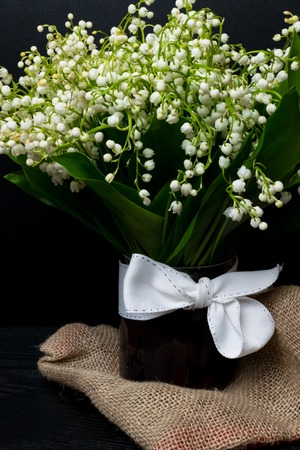 Lily of the valley flowers in glass vase, black background, selective focus, spring mood