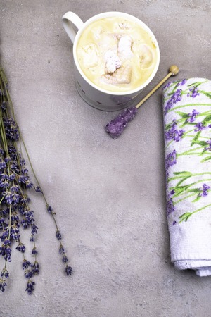 relax spa lavender mood with coffee, violet candy sugar on wooden stick, marshmallow, lavander print towel and bunch of flower.