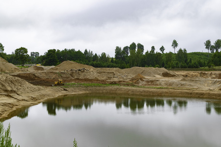 excavator working on sandpit earthmoving, sand quarry with water