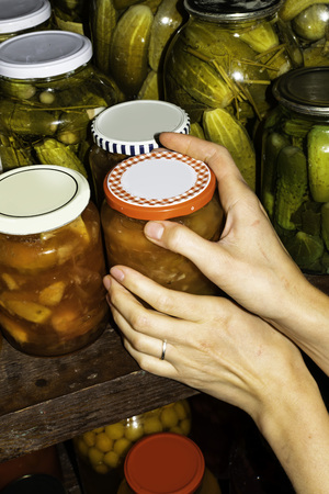 Woman puts jam jars in the basement, for storage for a long time. 免版税图像