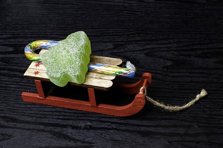 wooden toy sledge, surrounded by Christmas decor with marmalade green christmas tree 版權商用圖片