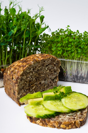 Whole Grain rye bread with seeds, green sprouts, and avocado sandwich, copy space, fibre rich food 写真素材