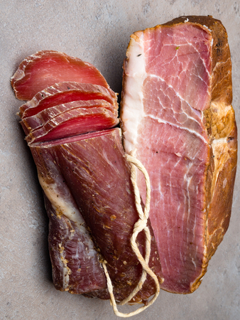 Smoked ham on table with garlic and biltong beef jerky piece on grey table Natural product from organic farm, produced by traditional methods