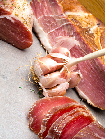 Smoked ham, jerky corned beef on table with garlic, thyme herb Natural product from organic farm, produced by traditional methods Stock Photo