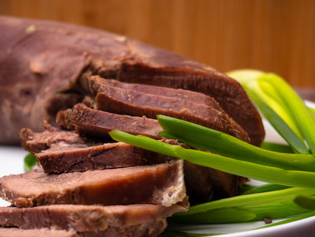 Boiled beef tongue with green onion is served on a plate in a restaurant on white plate Foto de archivo