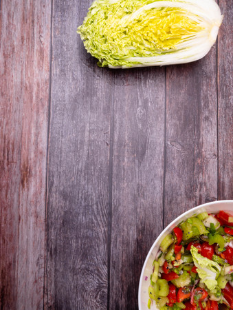Fresh vegetable salad of chinese cabbage, tomato, pepper and onion with olive or sunflower oil on wooden table. Healthy food. Top view Foto de archivo