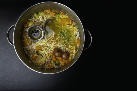 White soup noodles with onion, celery, carrot, sweet Potatoes, broccoli, pumpkin, ,icrogreen spices. On a black Board.