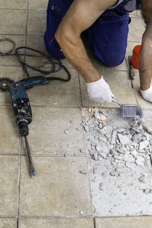 Men worker are extracting, drilling tiles with perforator on veranda, selective focus