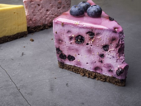Blueberry cheesecake on concrete with blueberries, at background yellow and pink cakes, selective focus Reklamní fotografie