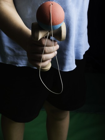 Classic Japanese game kendama, boy hands playing blue and pink color kendama
