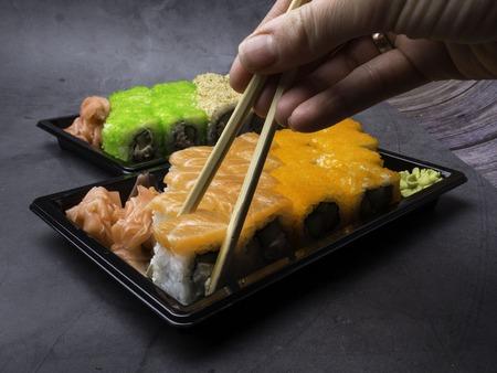 Japanese sushi on a dark background. Sushi rolls, pickled ginger, wasabi. Sushi set on a table. Space for text. sushi background. Asian or Japanese food.