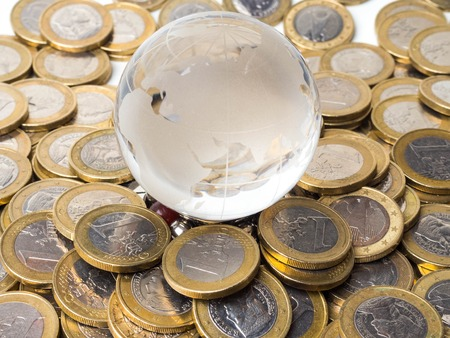 World globe and coins stack - Concept of balance between planetary health and economic growth Archivio Fotografico