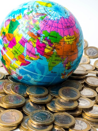 Pile of coins with world planet on the background - Concept of saving the planet, concept of relationship between money, economic growth and planet earth