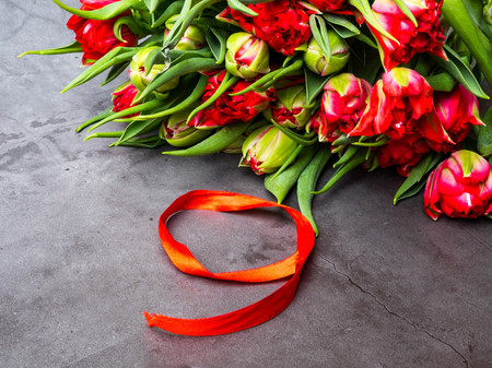 red tulips with red ribbon isolated on concrete background. Victory day or Fatherland defender day, 9 may symbol Banco de Imagens