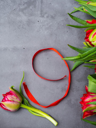 red tulips with red ribbon isolated on concrete background. Victory day or Fatherland defender day, 9 may symbol 写真素材