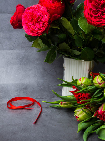 red tulips, roses in white vase and roses with red ribbon isolated on concrete background. Victory day or Fatherland defender day, 9 may symbol Banco de Imagens