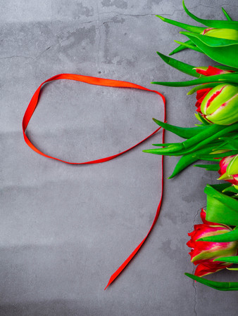 9 May background - red tulips bunch and red ribbon on the concrete background, free space for text