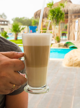 Coffe time. Hand of man hold coffee latte or cappuccino in the morning, Coffee drink. Close up of a man hands holding a hot glass. Closeup Stock Photo