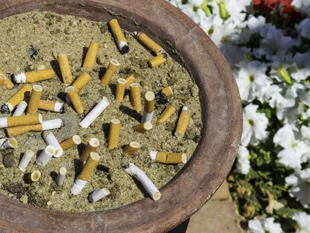 Smoked Cigarettes in the sand ashtray, Stop smoking Concept, unhealthy Stock Photo