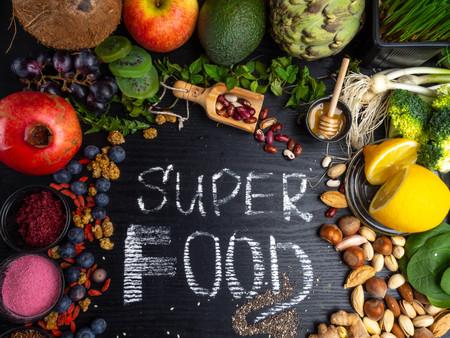 Sana selezione di super alimenti su sfondo di legno. Ad alto contenuto di antiossidanti, vitamine, minerali e antociani, vista dall'alto