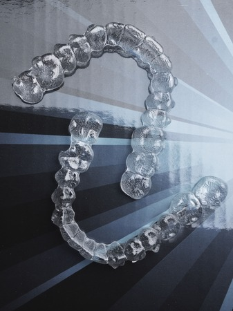 Invisible dental teeth brackets tooth aligners plastic braces retainers to straighten teeth. Orthodontic temporary removable straighteners in dental office dentists surgery Banco de Imagens