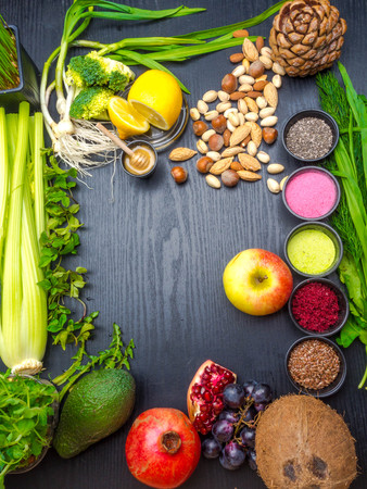 Various colorful superfoods as acai powder, matcha powder, spirulina, seeds, blueberry, dried goji berries, honey, giner, citrus, coconut, avocado, pomegranate selery dandelion nuts on dark background copy space