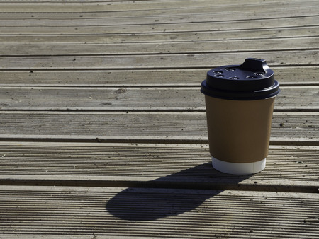 Cup of coffee to go on the wooden table. Street coffee copy space 版權商用圖片