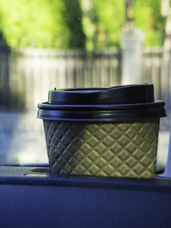 Coffee in the car salon. A single paper coffee cup inside the car cup holder and blurred nature view