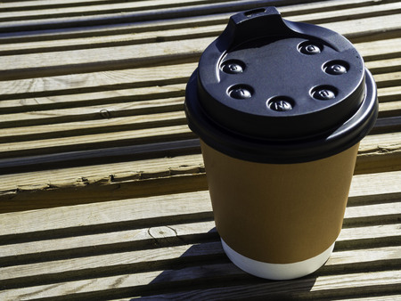 paper cup with lid. Coffe cup on wooden surface. Street coffee, take and go concept