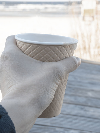 My favorite beverage. Close up female hand with paper cup of tea