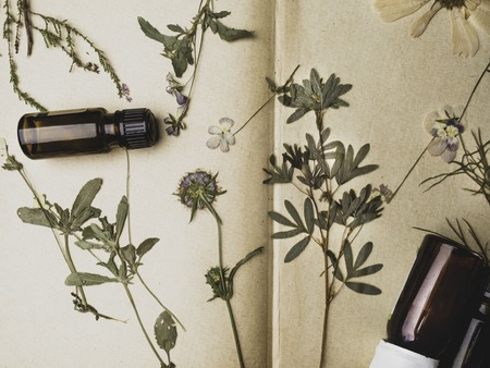 Vintage flower on old book background with essential oils, health and spa concept 版權商用圖片